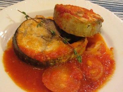 паламуд върху лук и домати с мащерка и розмарин